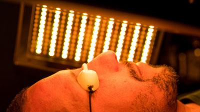Un homme en plein soin visage de photobiomodulation LED sous une lumière orange.