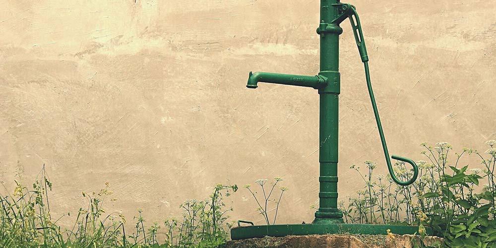 Grüne Wasserpumpe aus Metall, die auf einem Baumstumpf steht. | Jan Steiner - Pixabay