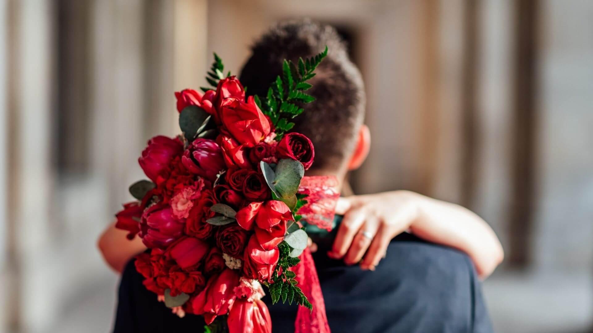 La mariée enlace son mari et montre son bouquet