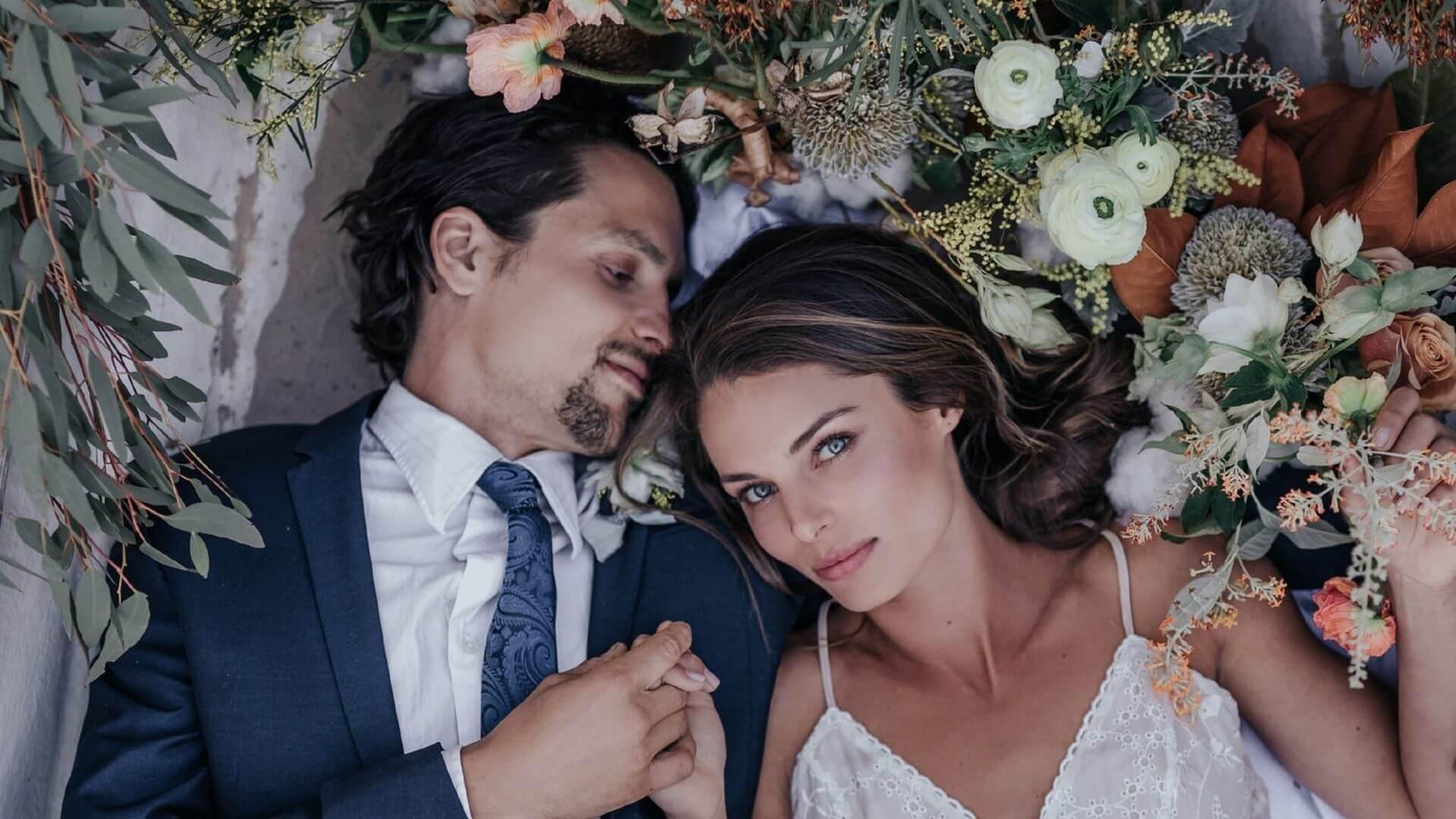 Les mariés allongés posent ensemble