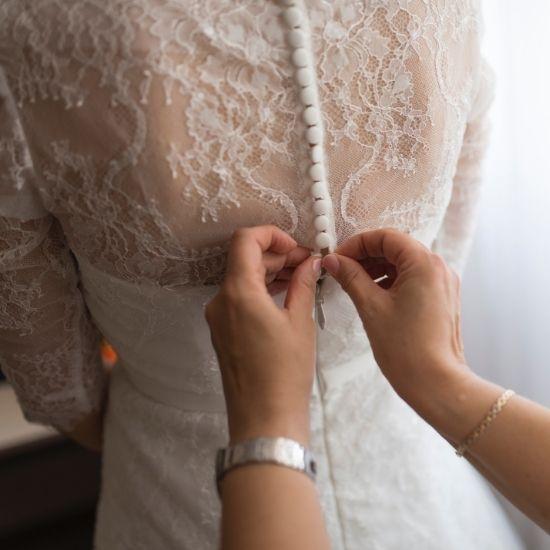 Une demoiselle d'honneur boutonne la robe de la mariée