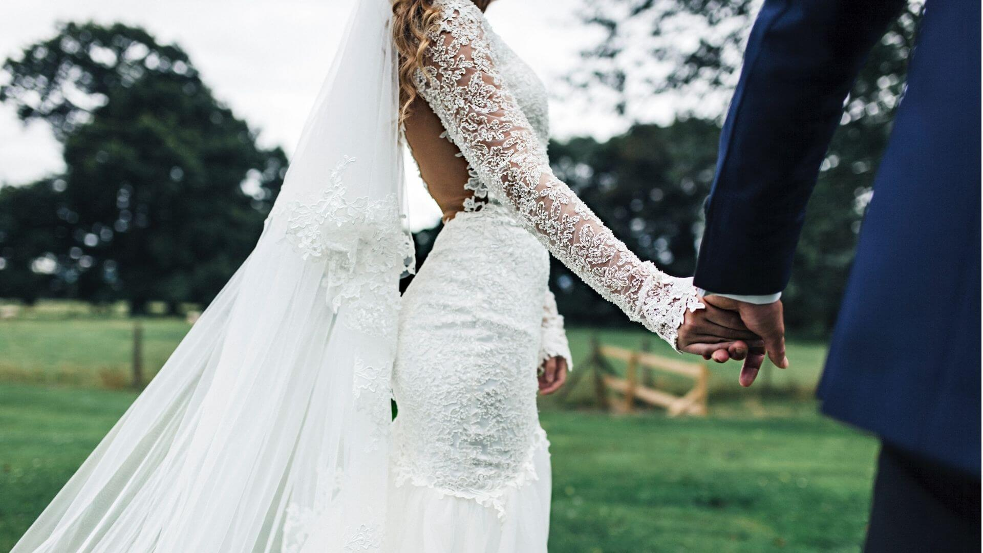 La mariée dans sa robe prend la main de son époux à Senlis