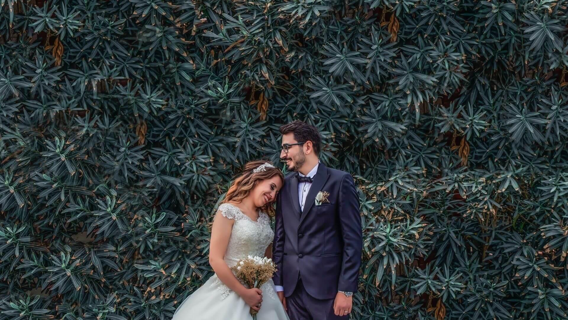 Un couple de mariés sourit devant des fleurs à Soissons
