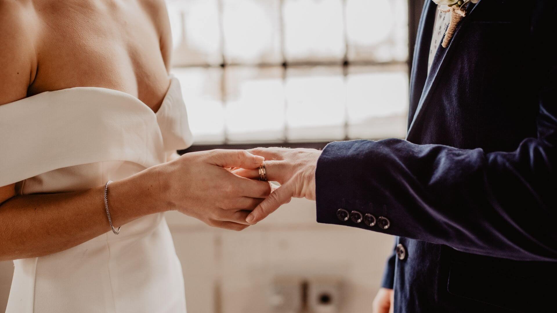 La mariée passe la bague de doigt de son époux à Versailles