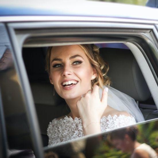 La mariée sourit dans sa voiture