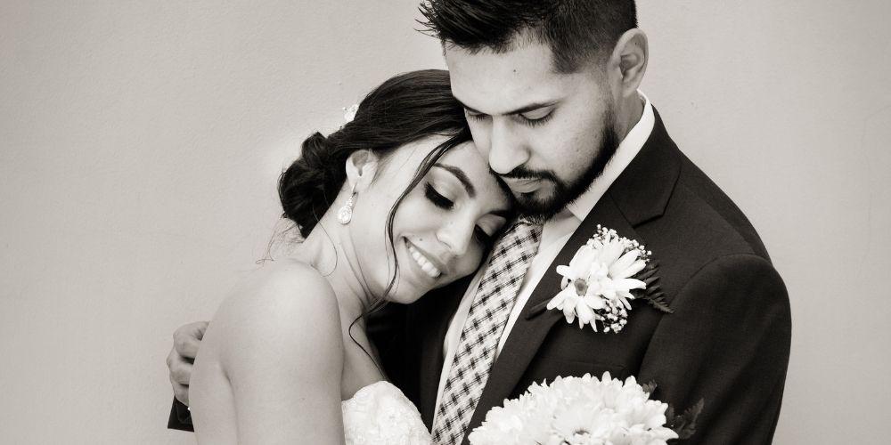 Un couple s'enlacent devant le photographe à leur mariage