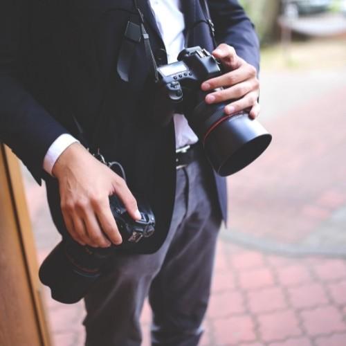 Un photographe de mariage tient son appareil