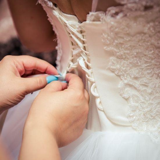 Une demoiselle d'honneur aide la mariée à fermer sa robe