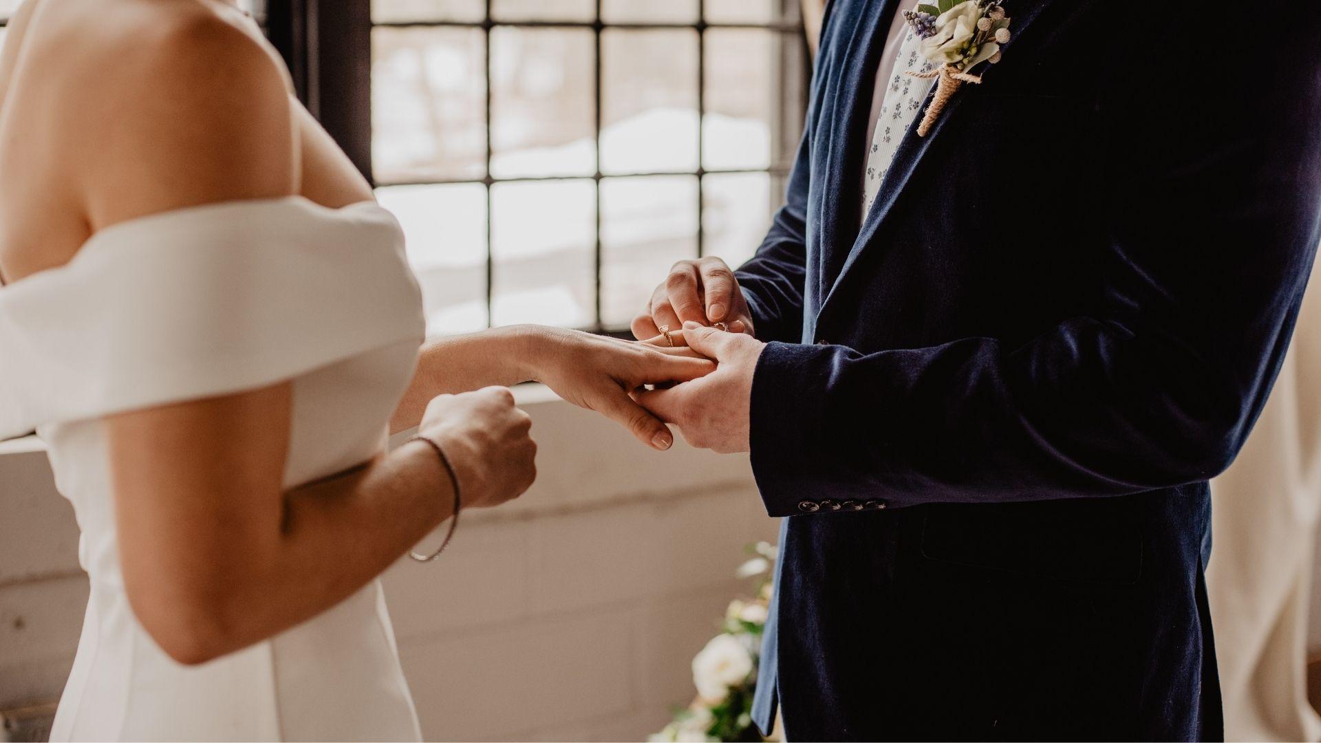 La marié passe la bague au doigt de la mariée à Paris 9