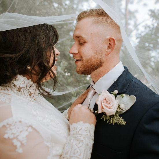 Les mariés se regardent sous le voile de la mariée
