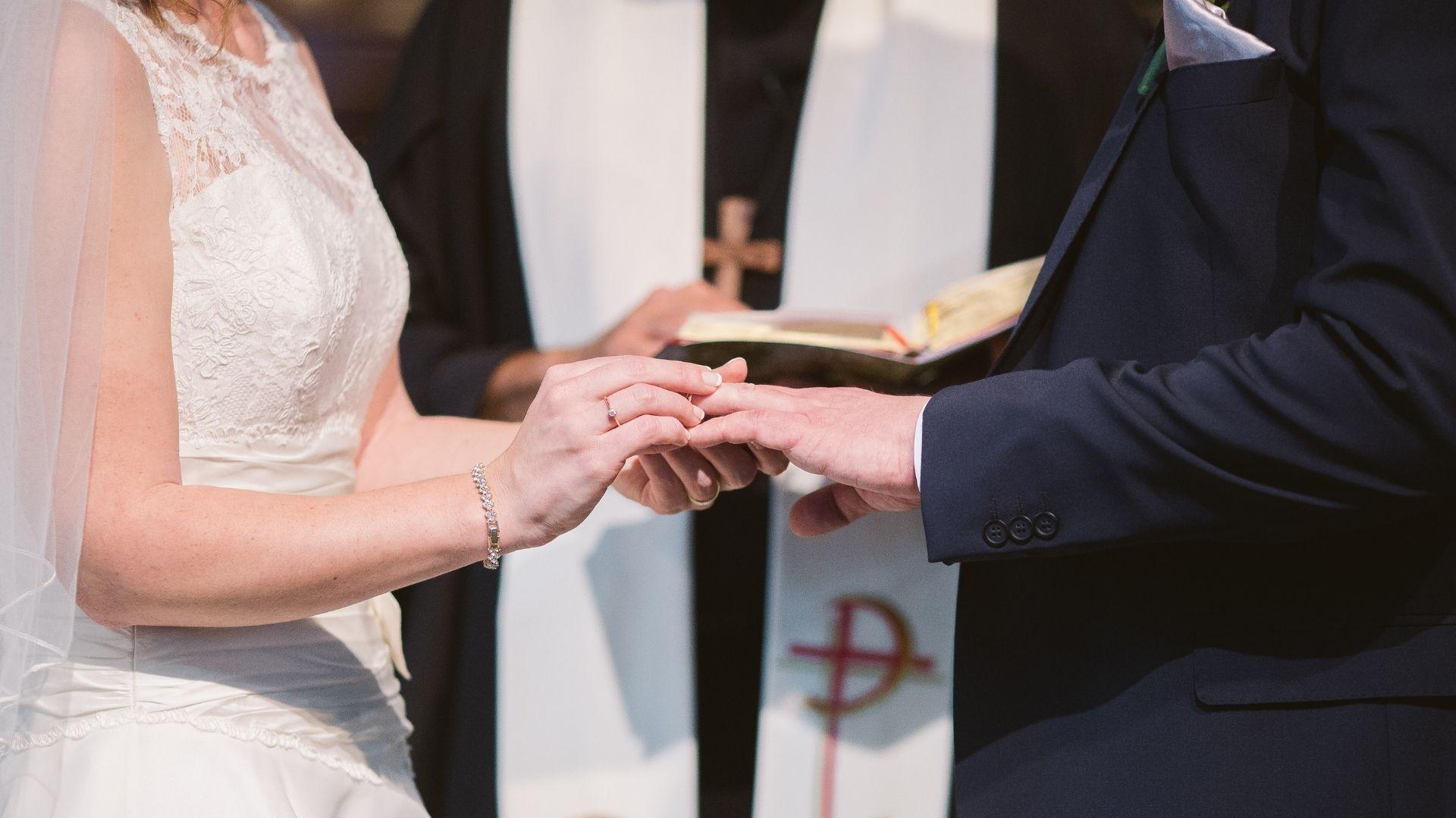 La mariée passe la bague au doigt du marié à Paris 18