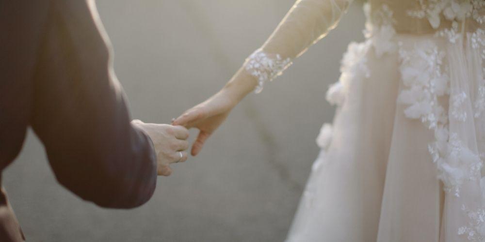 Les mariés se prennent la main, contents du coût de leur mariage