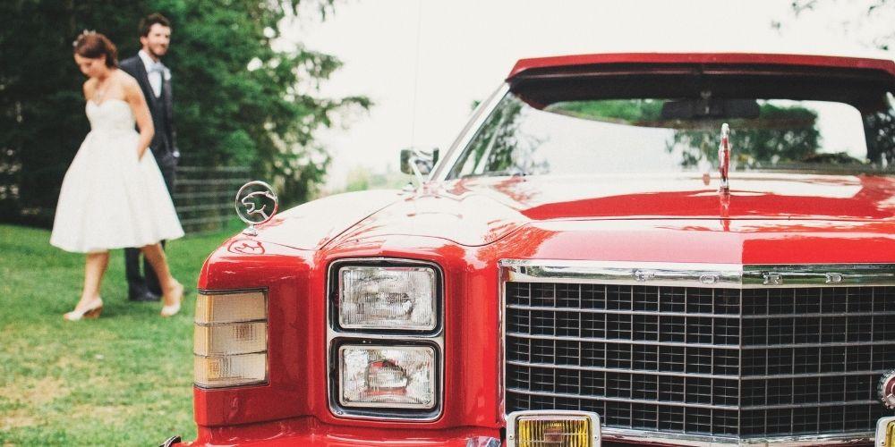 Les mariés quittent la marie dans leur voiture de mariage décorée