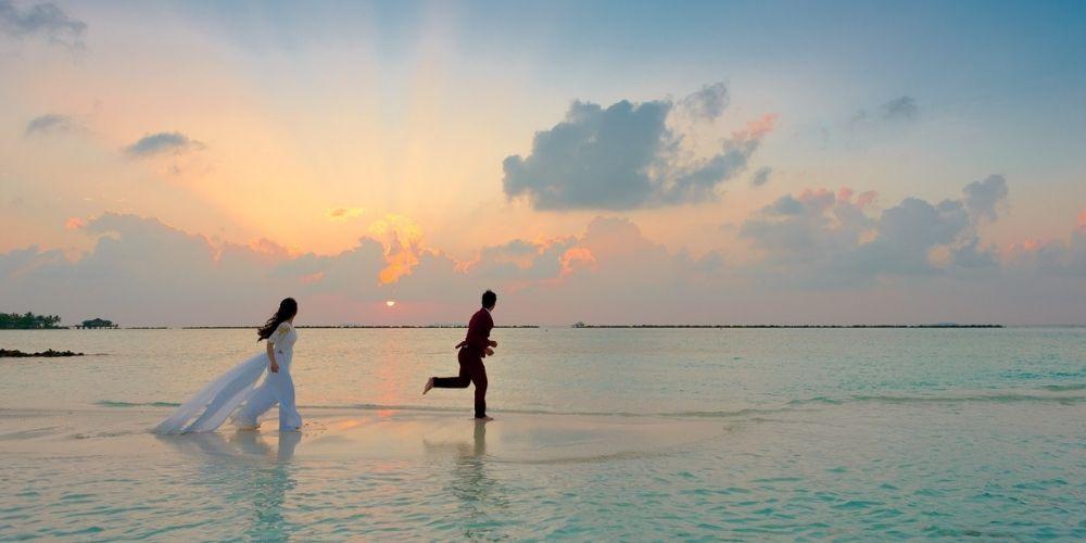 Les mariés ayant signé un contrat de mariage courent sur la plage