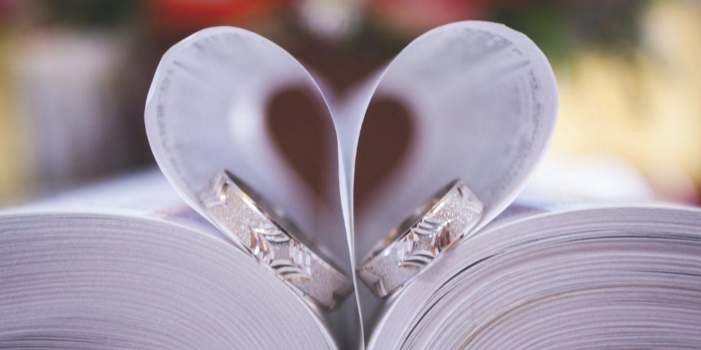 Photo des alliances dans des pages de livre en forme de cœur