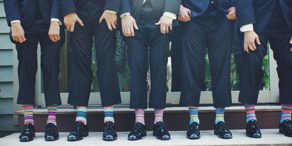 Le marié pose avec ses témoins et montrent ensemble leur chaussettes