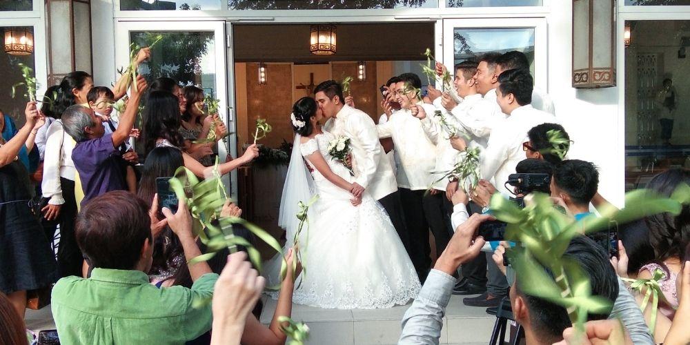 Le marié embrasse la mariée à la sortie de la cérémonie