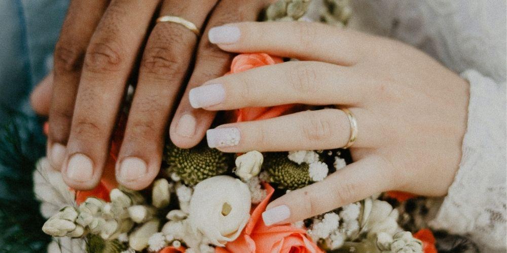 Les mariés montrent leur alliances sur leur bouquet