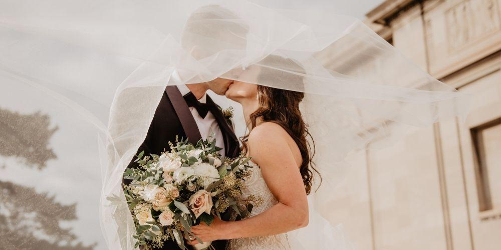 Les mariés s'embrassent, entourés du voile de la mariée