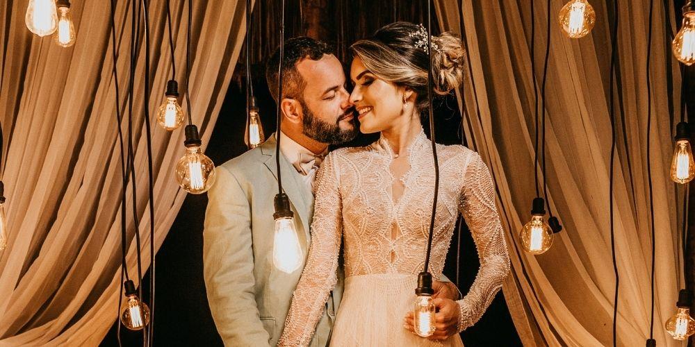 Un couple pose entourés de belles lumières pour une photo originale de mariage