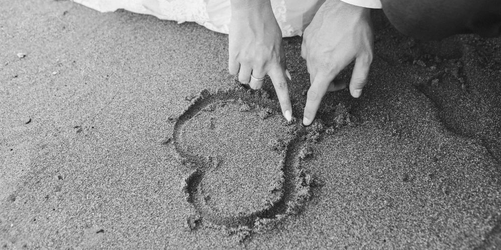 Les mariés dessinent un cœur dans le sable