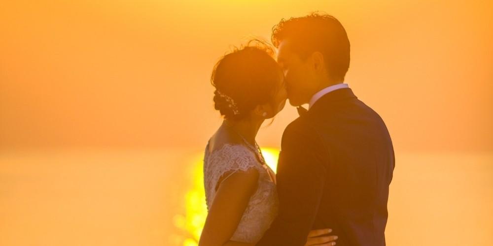 Les mariés posent devant un coucher de soleil sur la plage