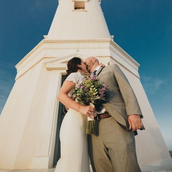 Les mariés s'embrassent devant un phare