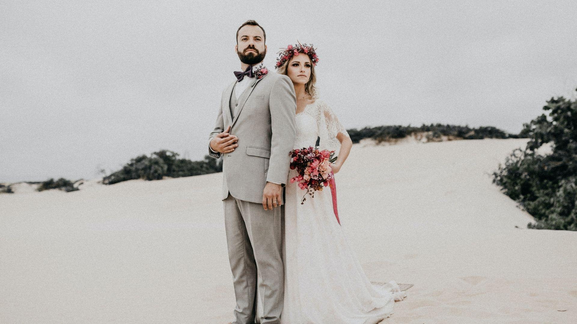 Les mariés posent sur le sable en Normandie