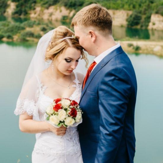 Les mariés se tiennent serrés devant un lac