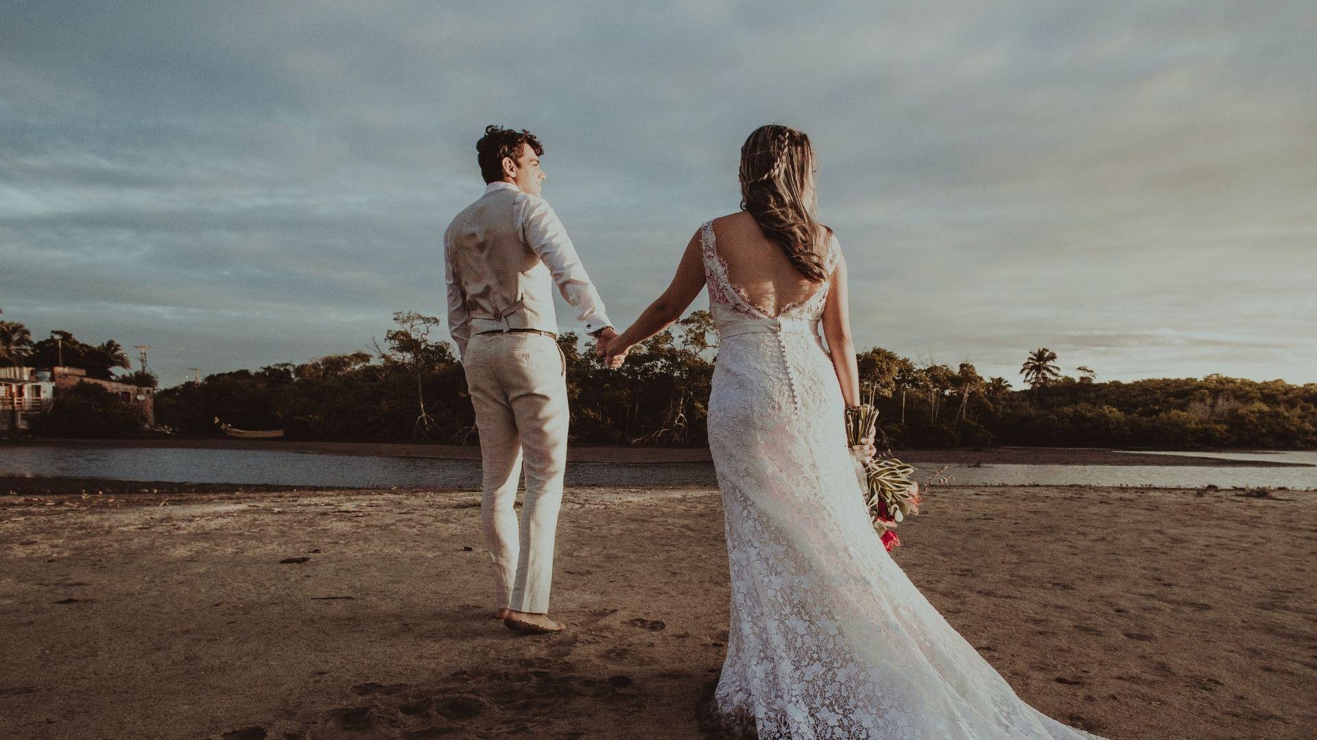 Les mariés marchent main dans la main sur une plage du Finistère