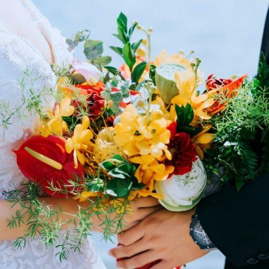 Les mariés tiennent ensemble le bouquet