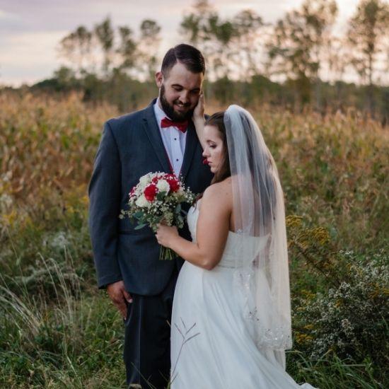 Les mariés posent dans un pré