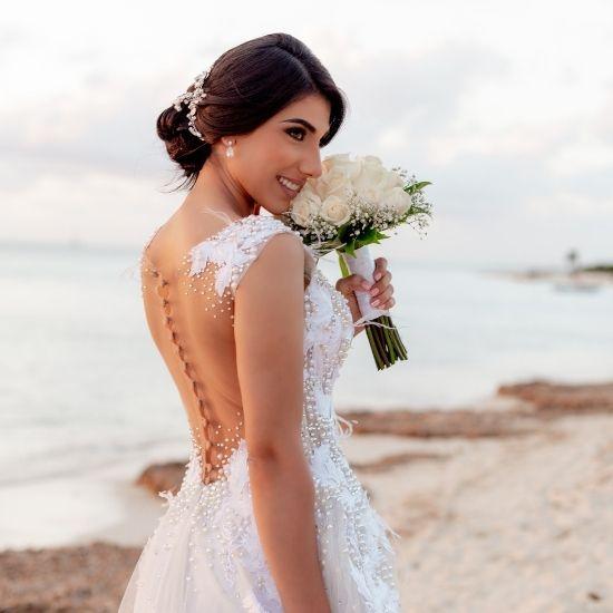 La mariée pose avec son bouquet sur la plage