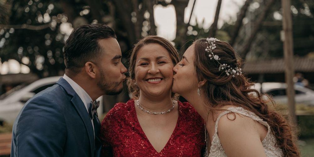 Les mariés embrassent de chaque côté la mère du marié