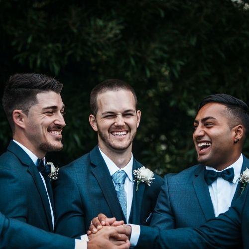 Le marié pose avec ses témoins et sourit