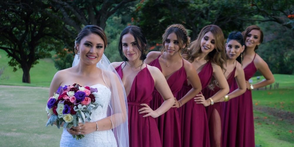 La mariée pose avec ses demoiselles d'honneur en file indienne