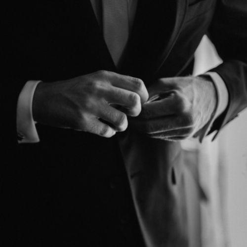 Photo du marié boutonnant sa veste durant les préparatifs de son mariage