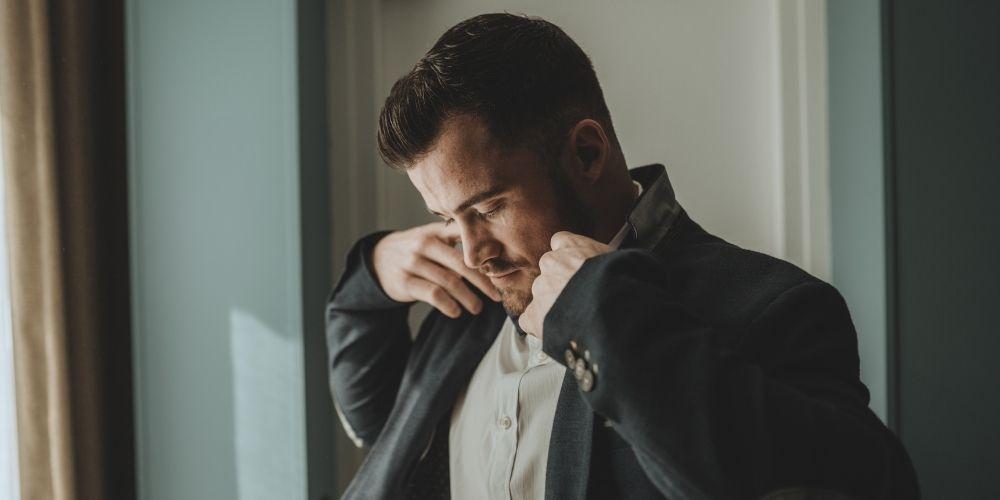 Photo du marié qui met sa veste durant les préparatifs de son mariage