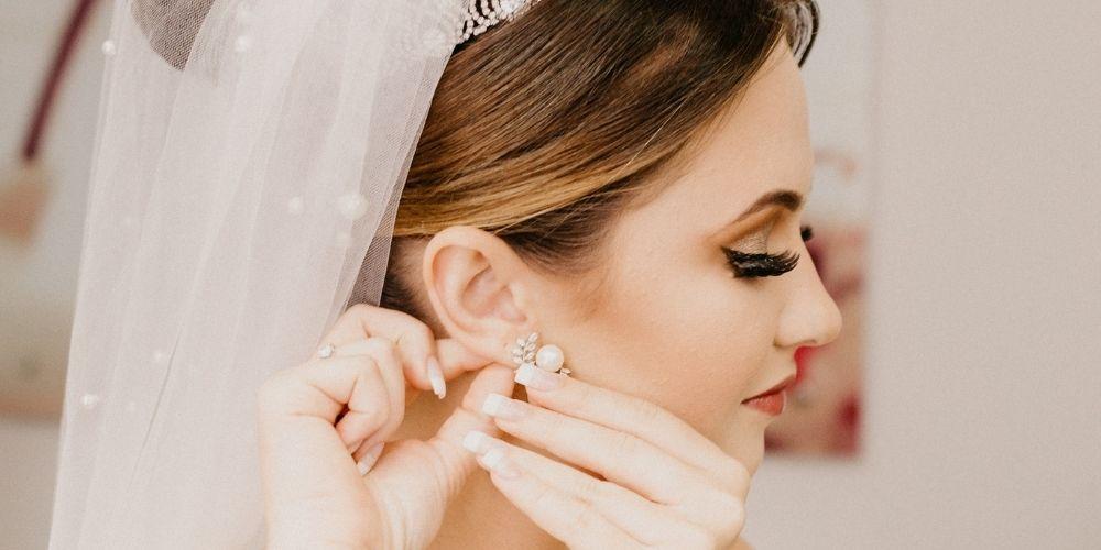 La mariée met sa boucle d'oreille durant ses préparatifs