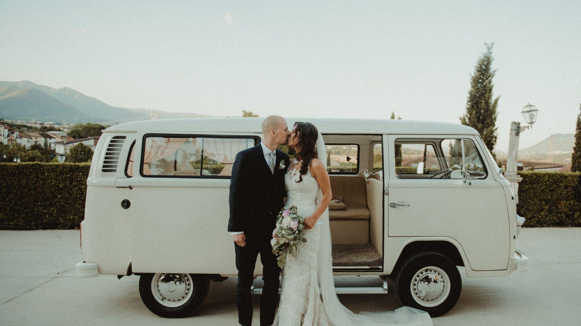 Les mariés s'embrassent devant un minivan en Bretagne