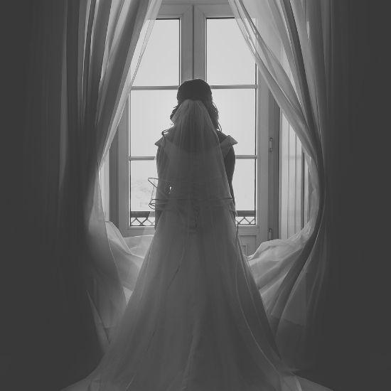 La mariée pose seule devant une fenêtre