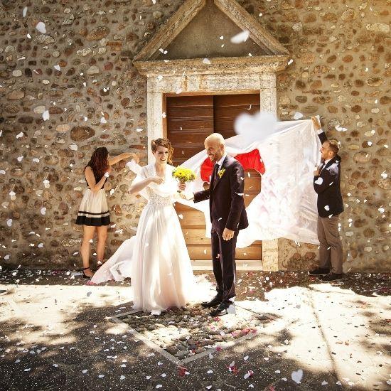 Les mariés sortent sous une pluie de confettis