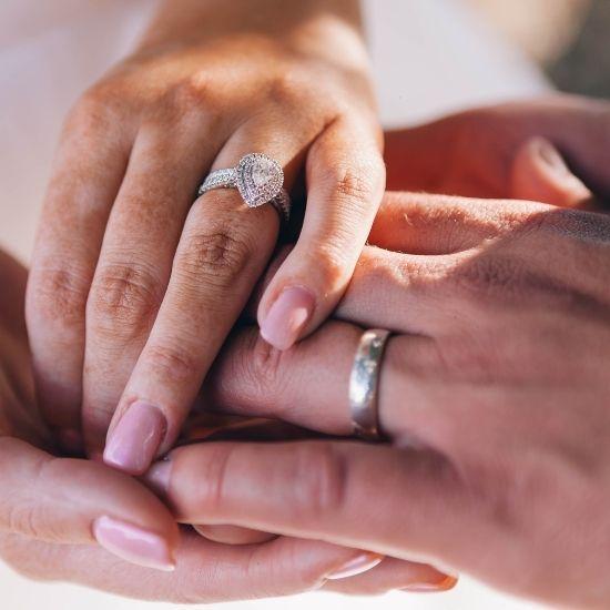 Photo des mains des mariés portant leur bague