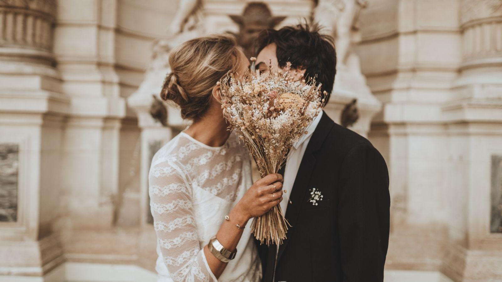 Les mariés s'embrassent derrière le bouquet à Tours