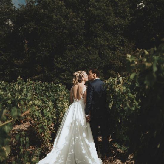 Les mariés s'embrassent dans un champ