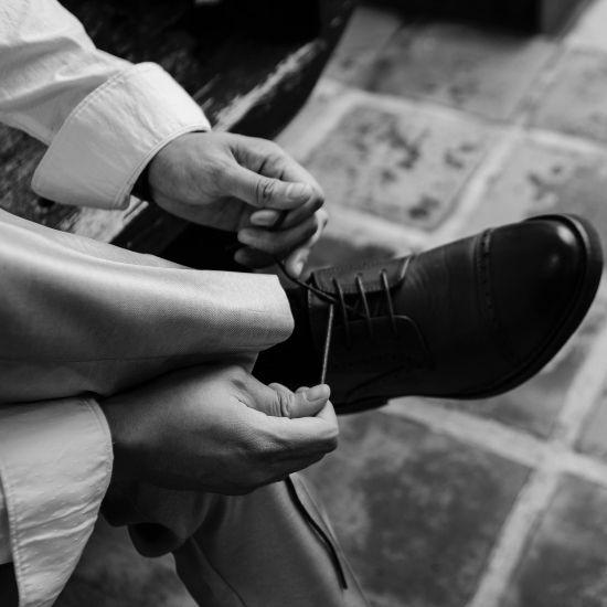 Photo du marié laçant sa chaussure