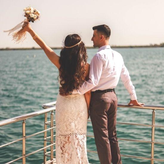 Les mariés posent de dos sur un bateau