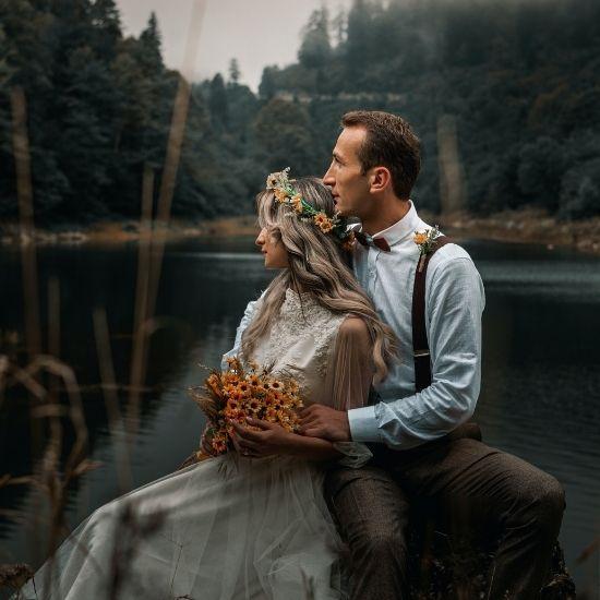 Photo des mariés posant au bord d'un lac