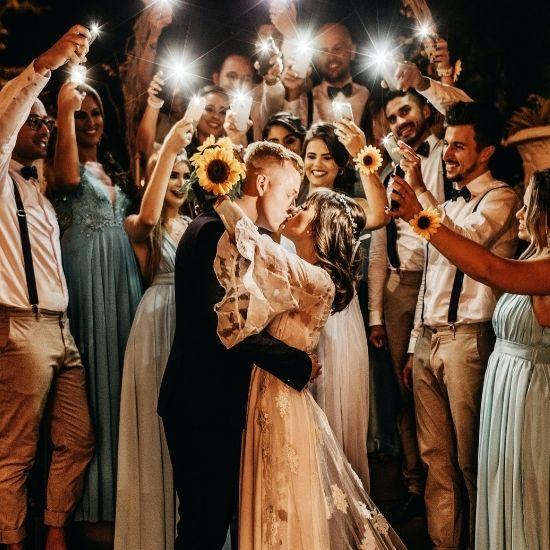 Les mariés s'embrassent sous les flashs de leurs invités