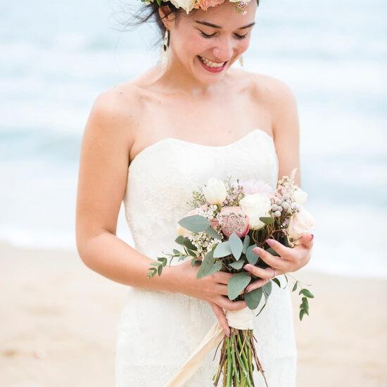 La mariée tient son bouquet en souriant